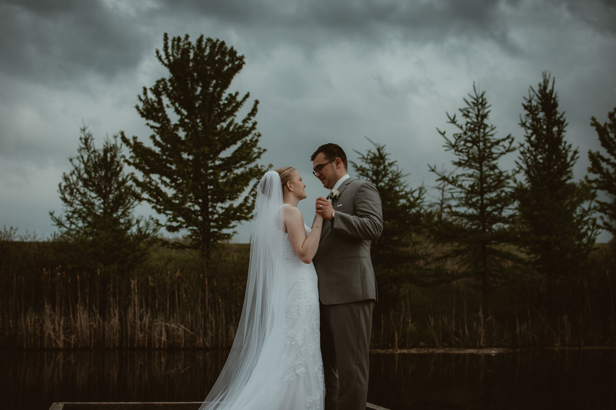 Bride and groom dancing on the dock of a pond with stormy clouds in the background