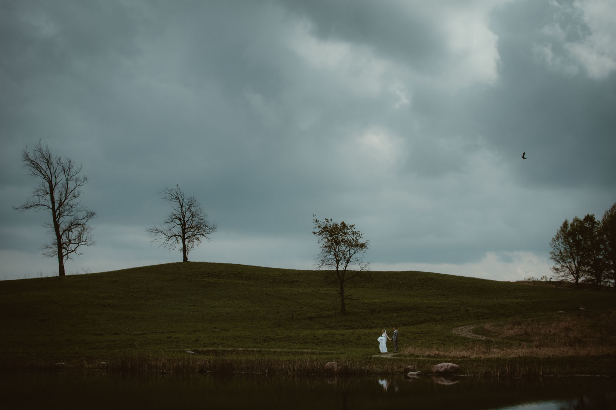 Landscape with couple walking along a pond as storm clouds roll in