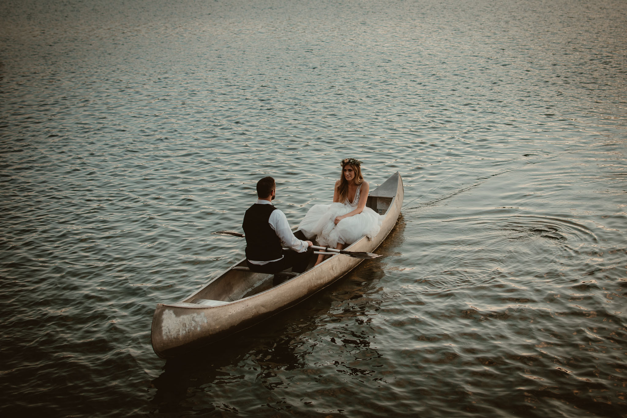 Bride and groom on an intimate sunset canoe voyage