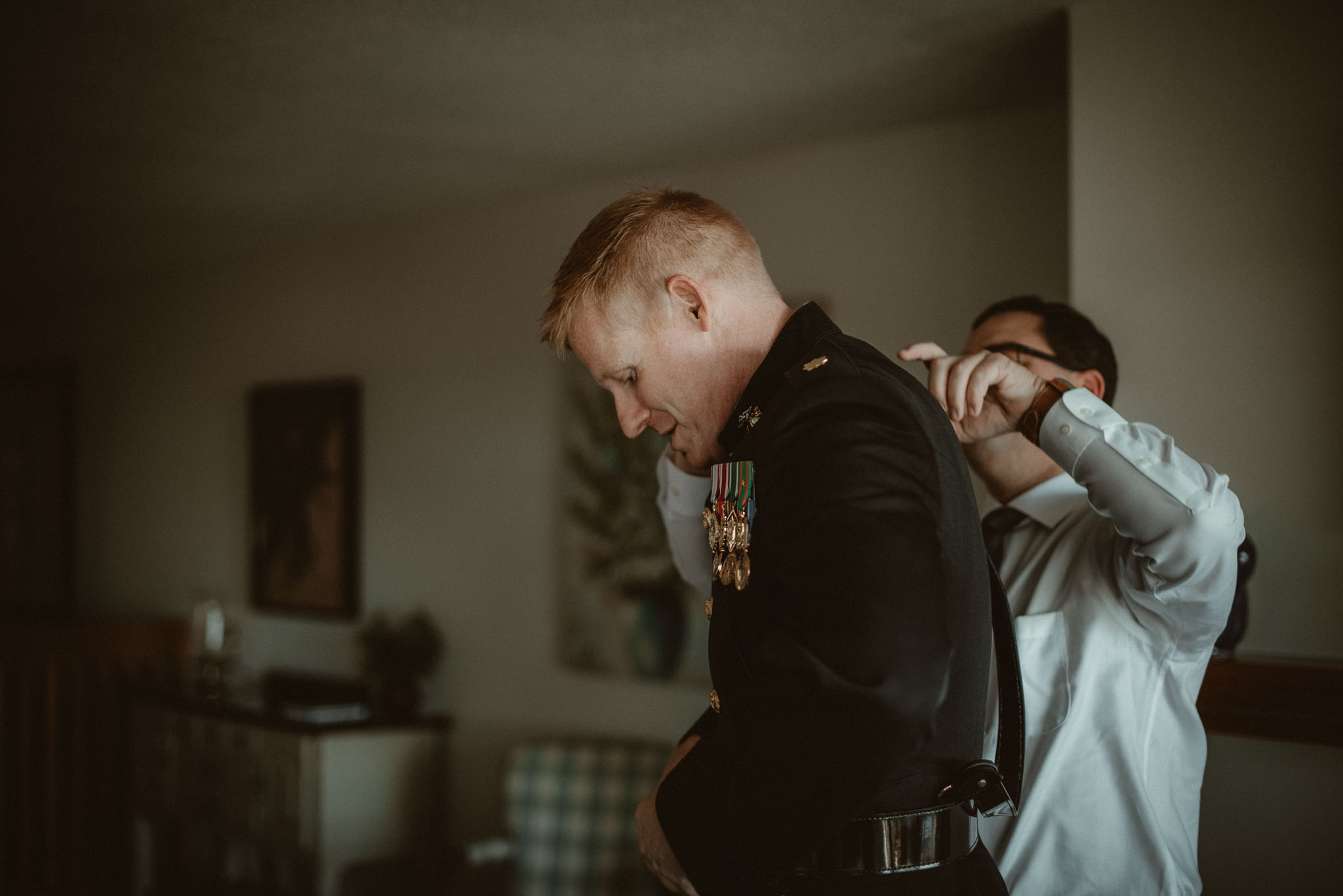 Best man helping the groom with his dress blues suit.