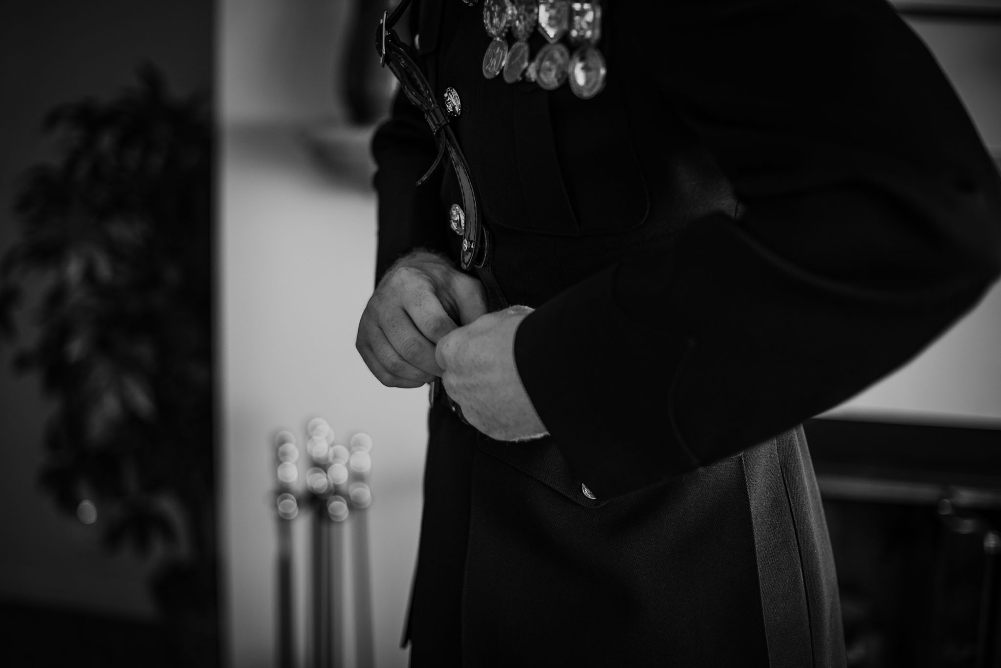 Black and white of groom buttoning his suit coat.