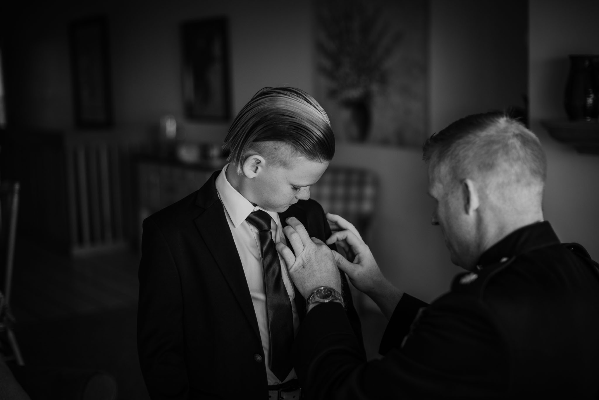 The groom helping his son with his boutonniere.