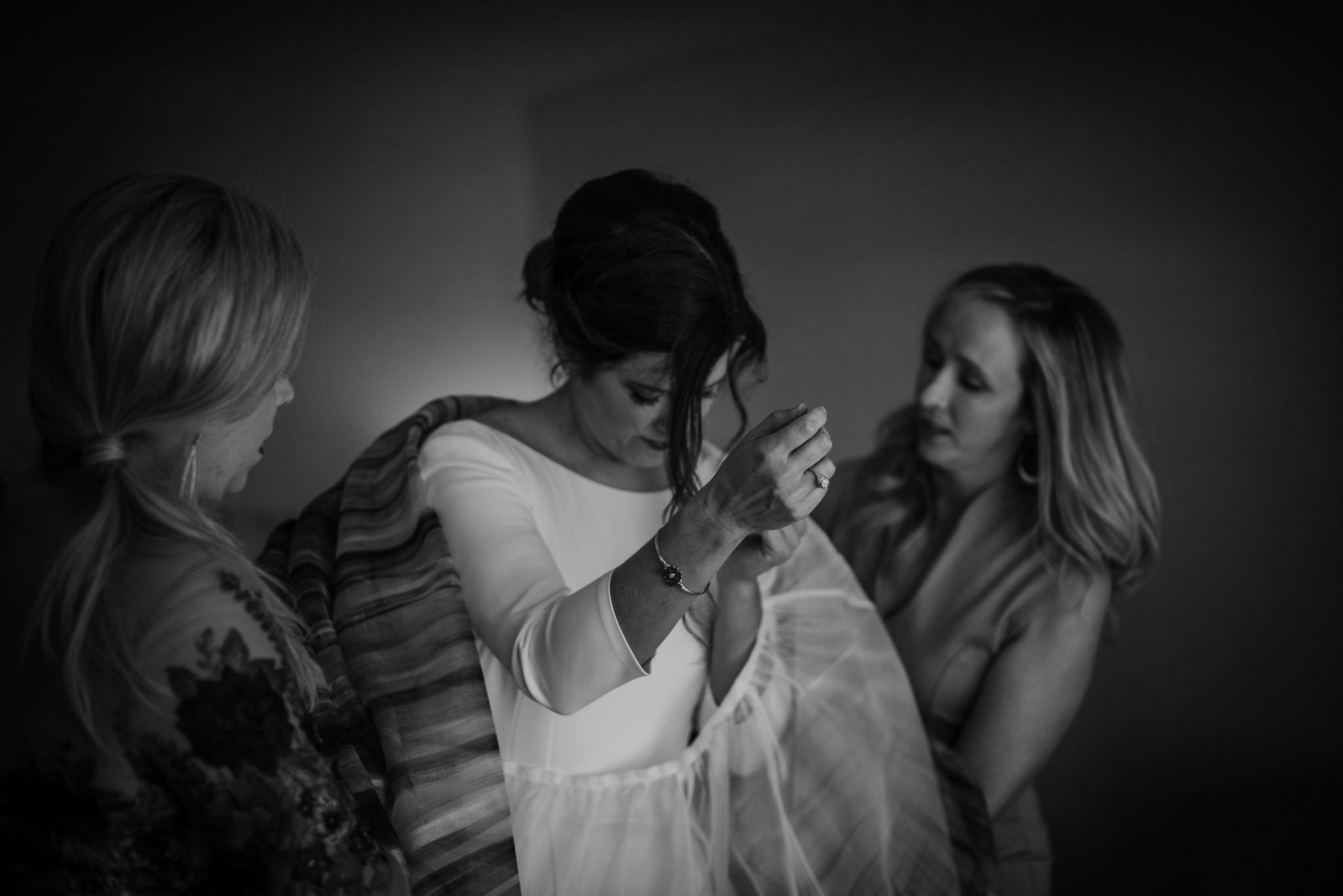 Bride's girlfriends helping her into her wedding dress.