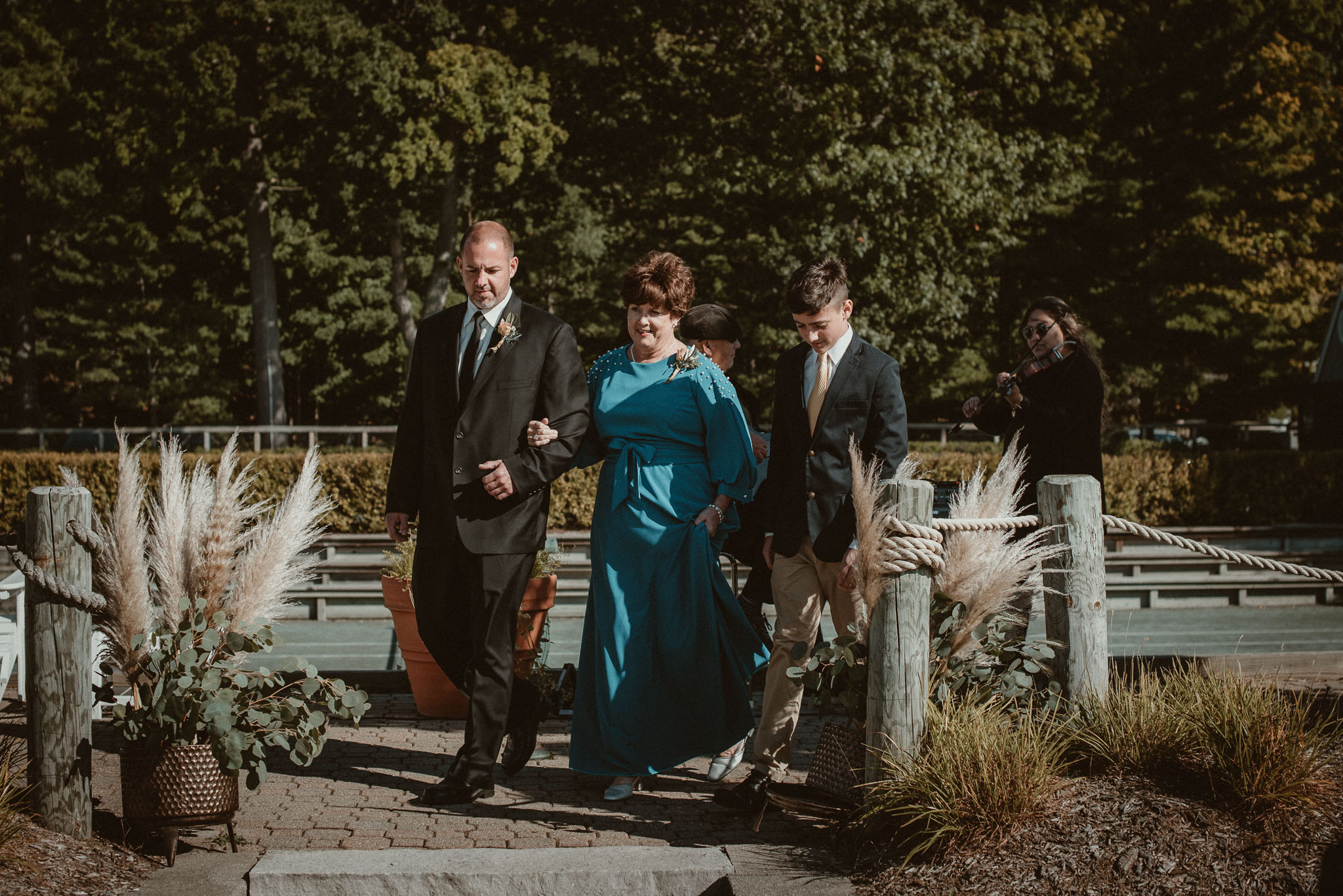 The mother of the bride being ushered to her seat by the bride's brother and his son.