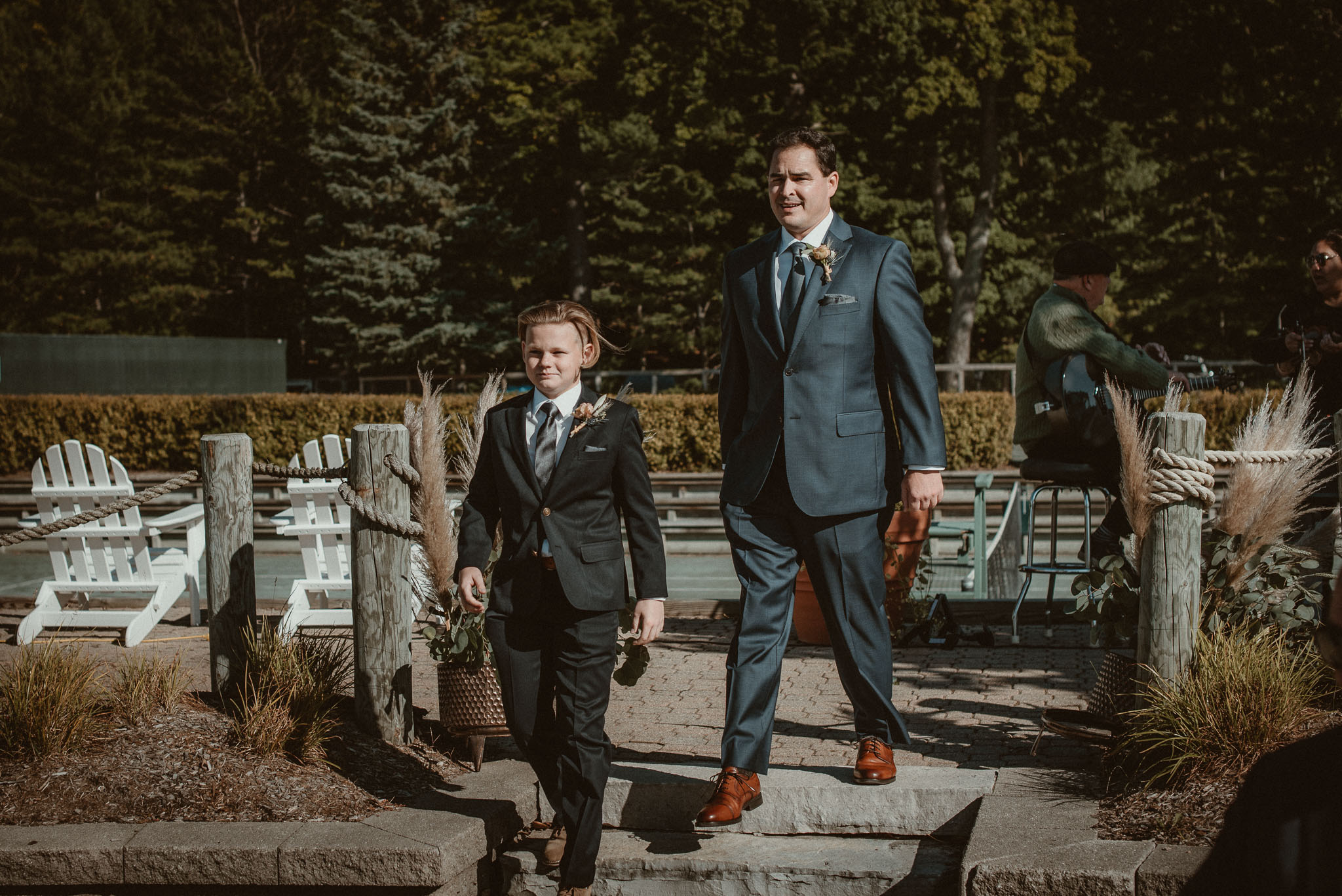 The groom's son and best friend as best men walking down the isle.