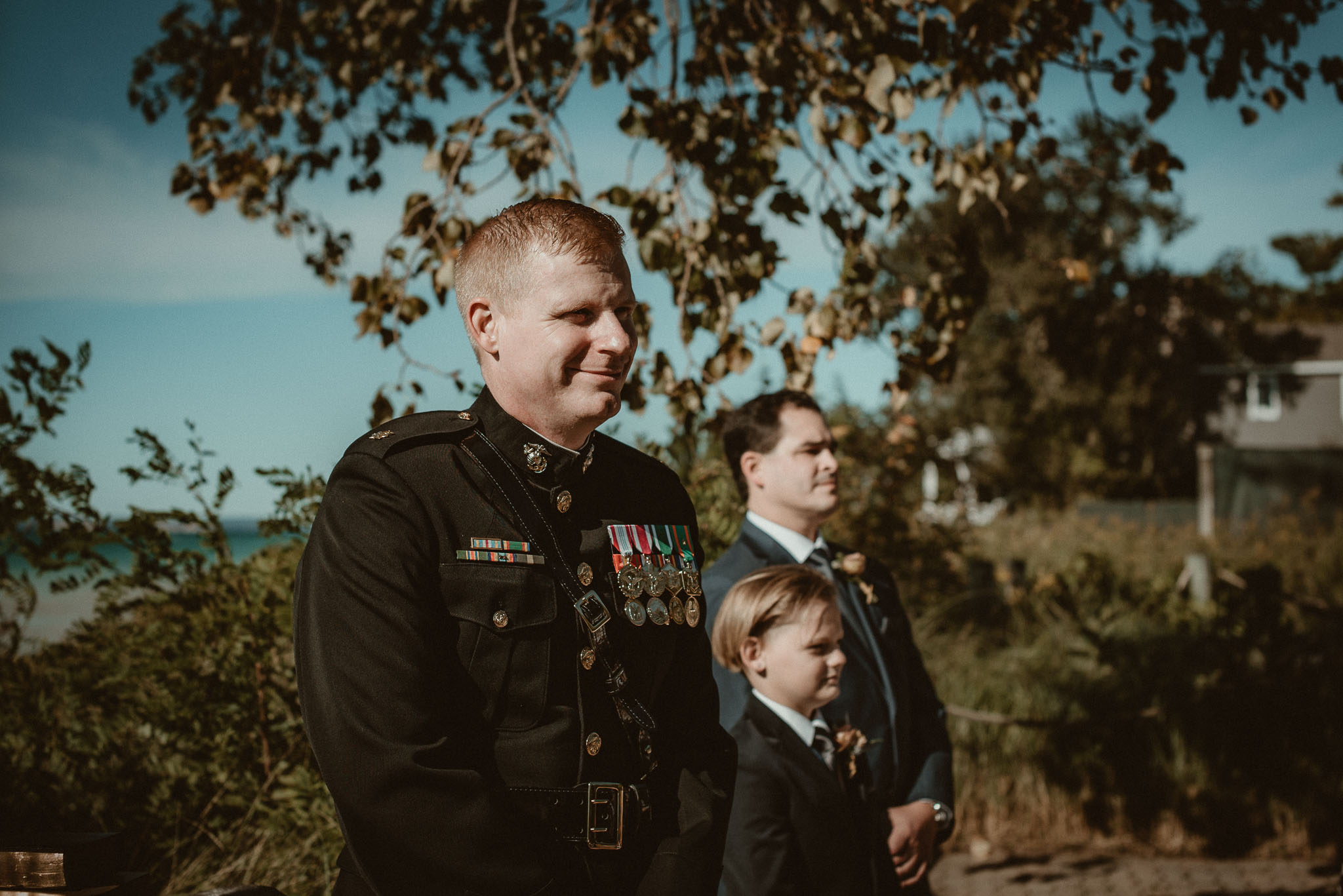The groom smiling, watching his bride being walked towards him by her father.
