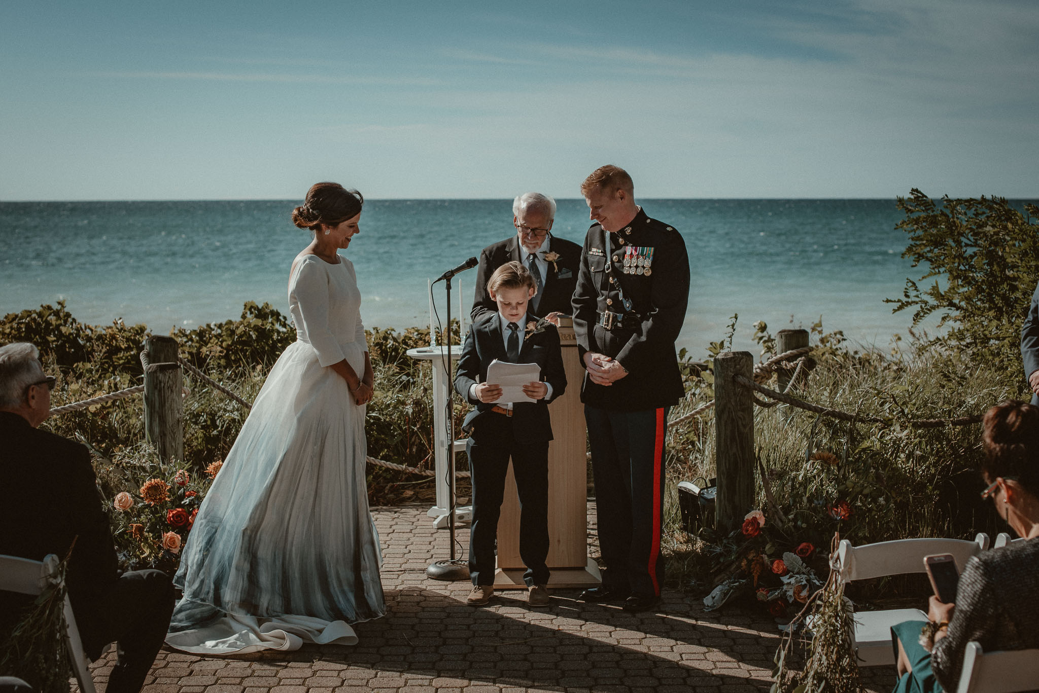 The groom's son standing between the couple as he reads a special message to his dad and future step mom.