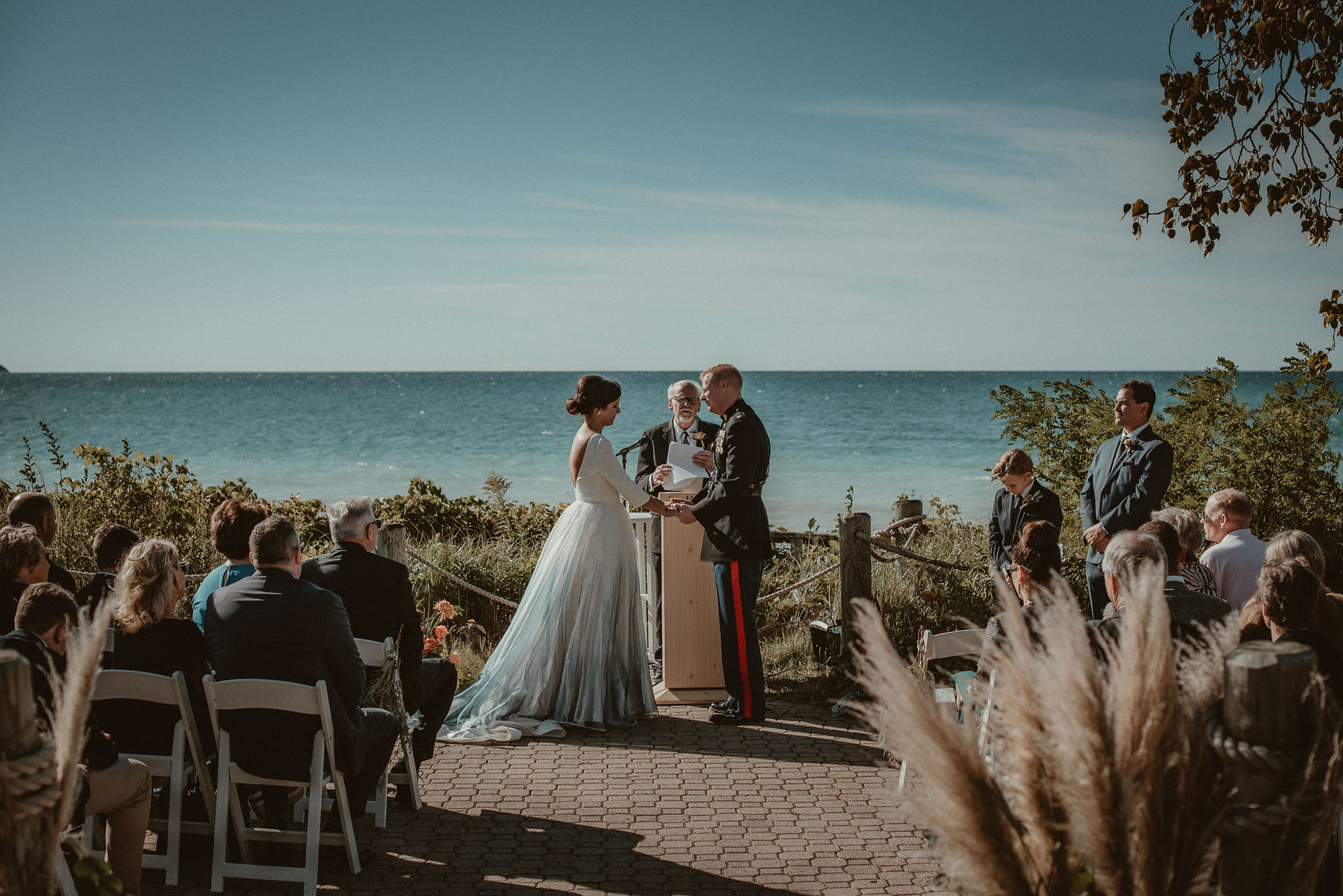 The bride and groom at the alter holding hands during the ceremony with Lake Michigan as a backdrop.