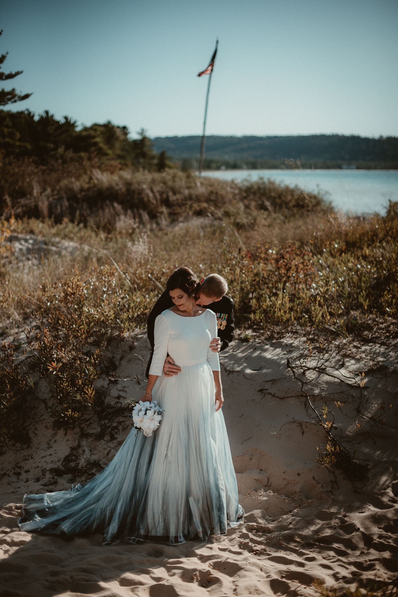 The groom kissing his brides shoulder holding her from behind with Lake Michigan in the background.