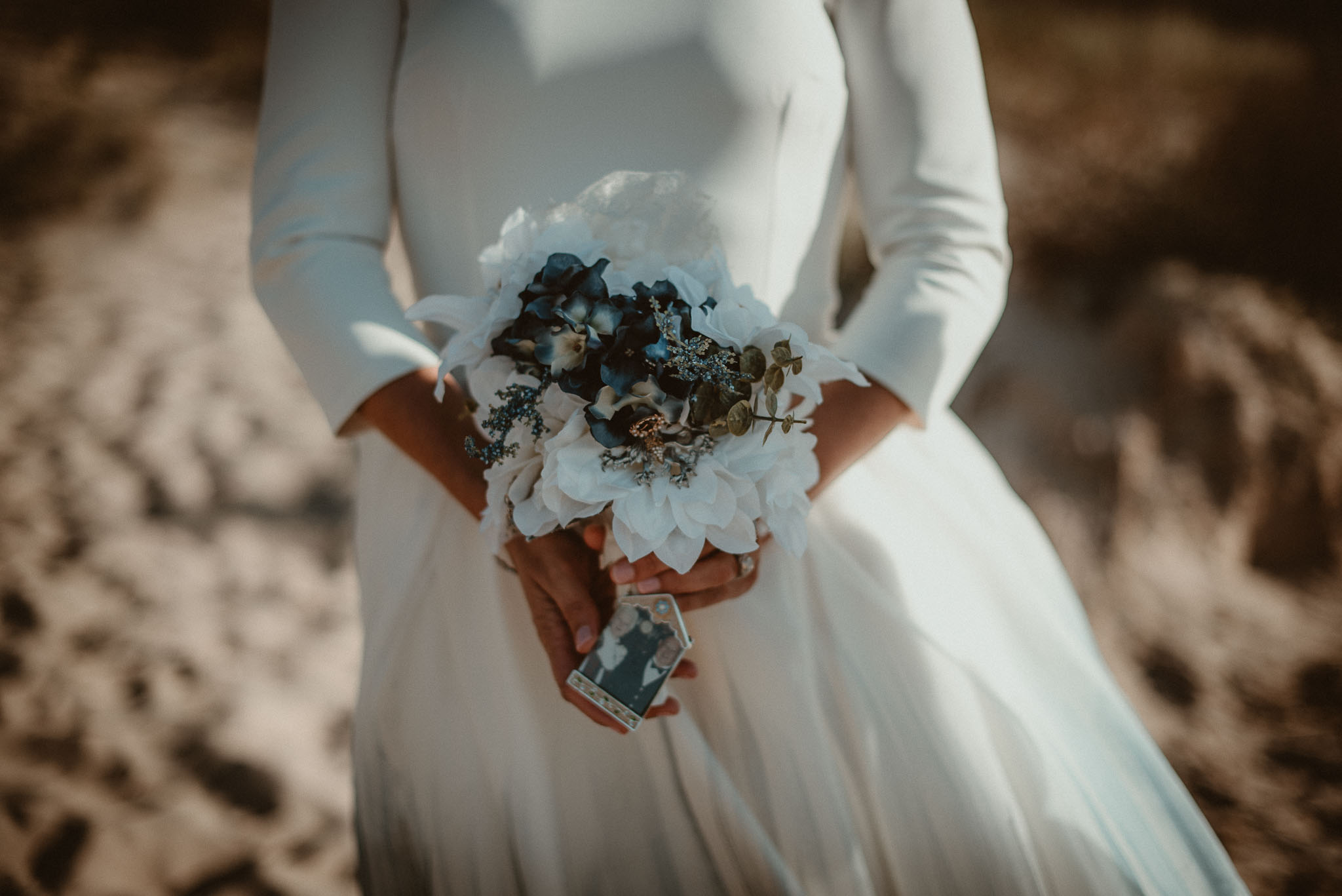 Bridal bouquet held in brides hands with photo of her late grandparents attached.
