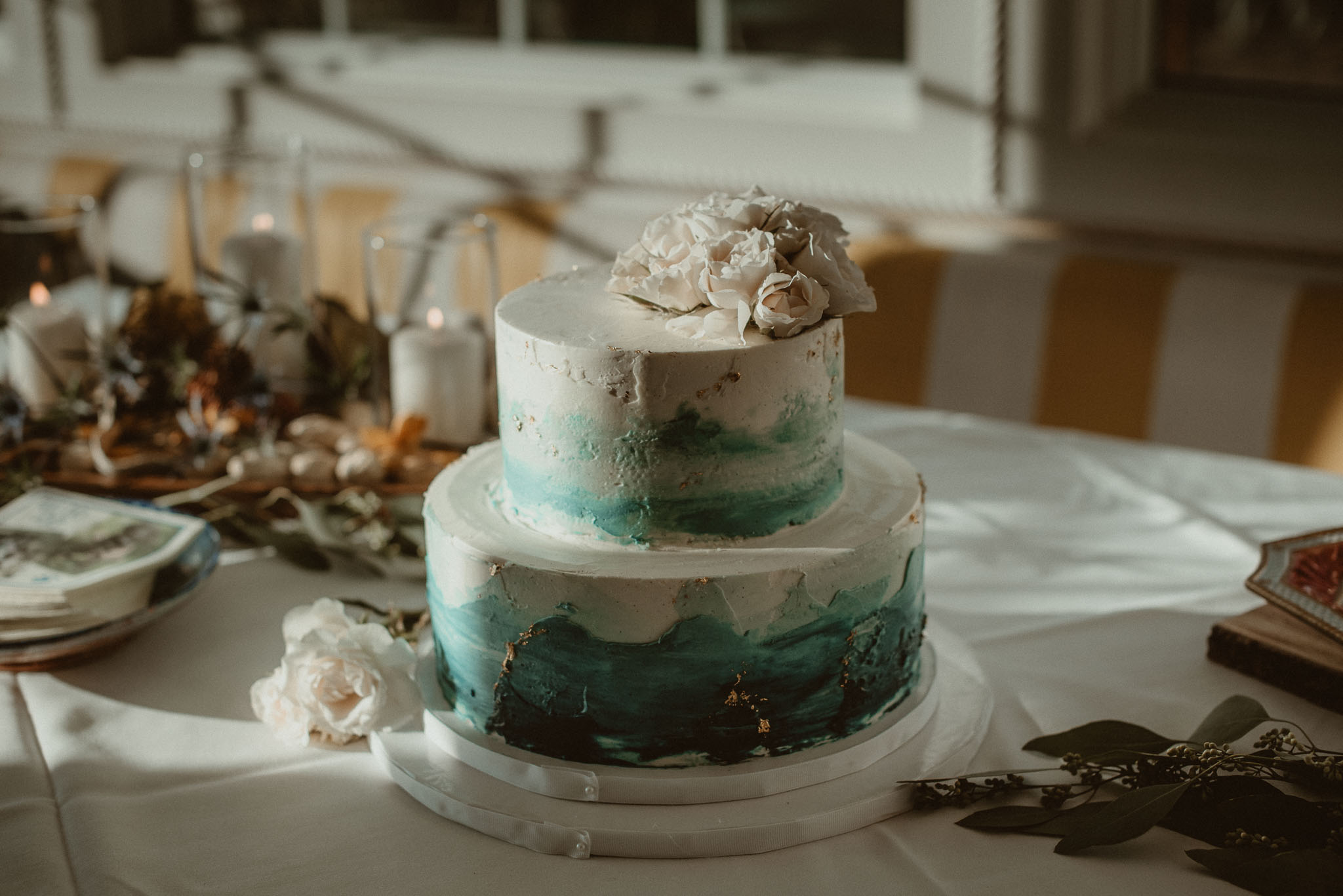 Small two tier wedding cake with fading Marine blue and flowers on top.