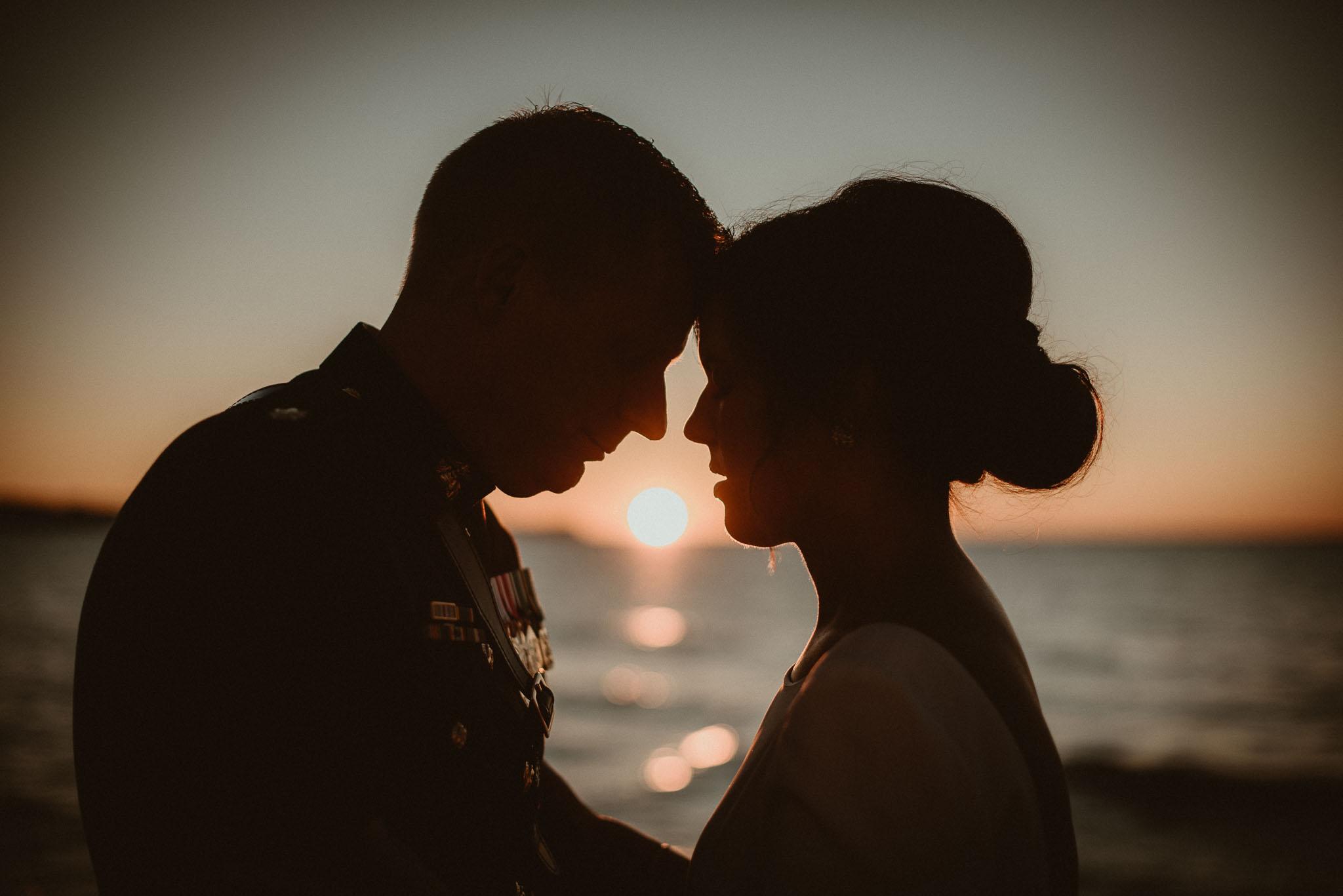 Sunset between bride and groom in silhouette.