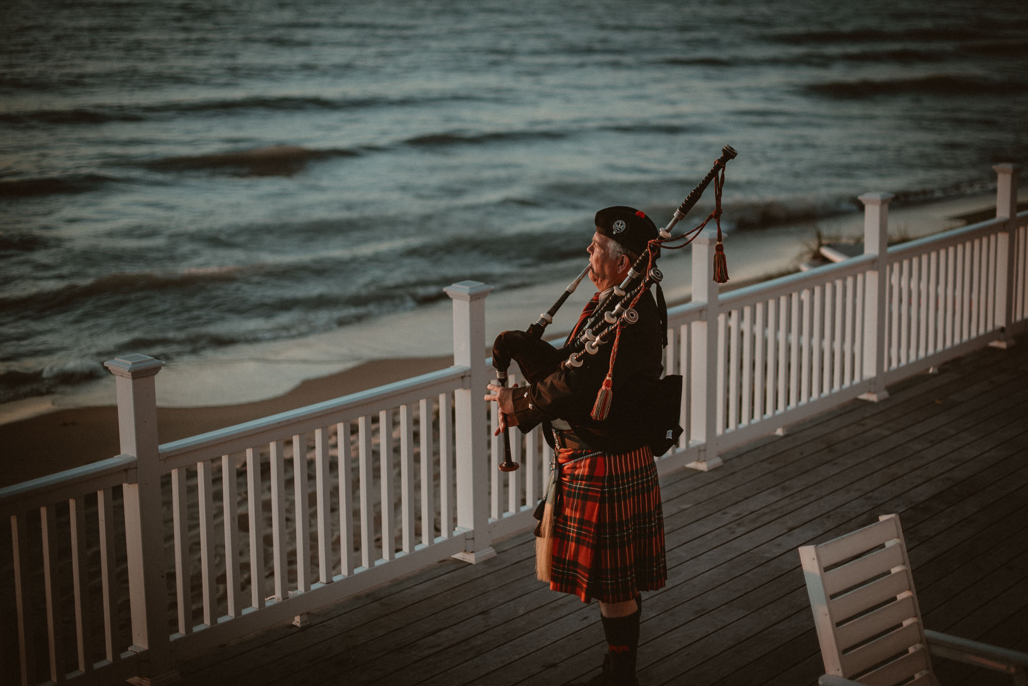 Bagpiper performing on the deck of Cafe Manitou at sunset on Lake Michigan