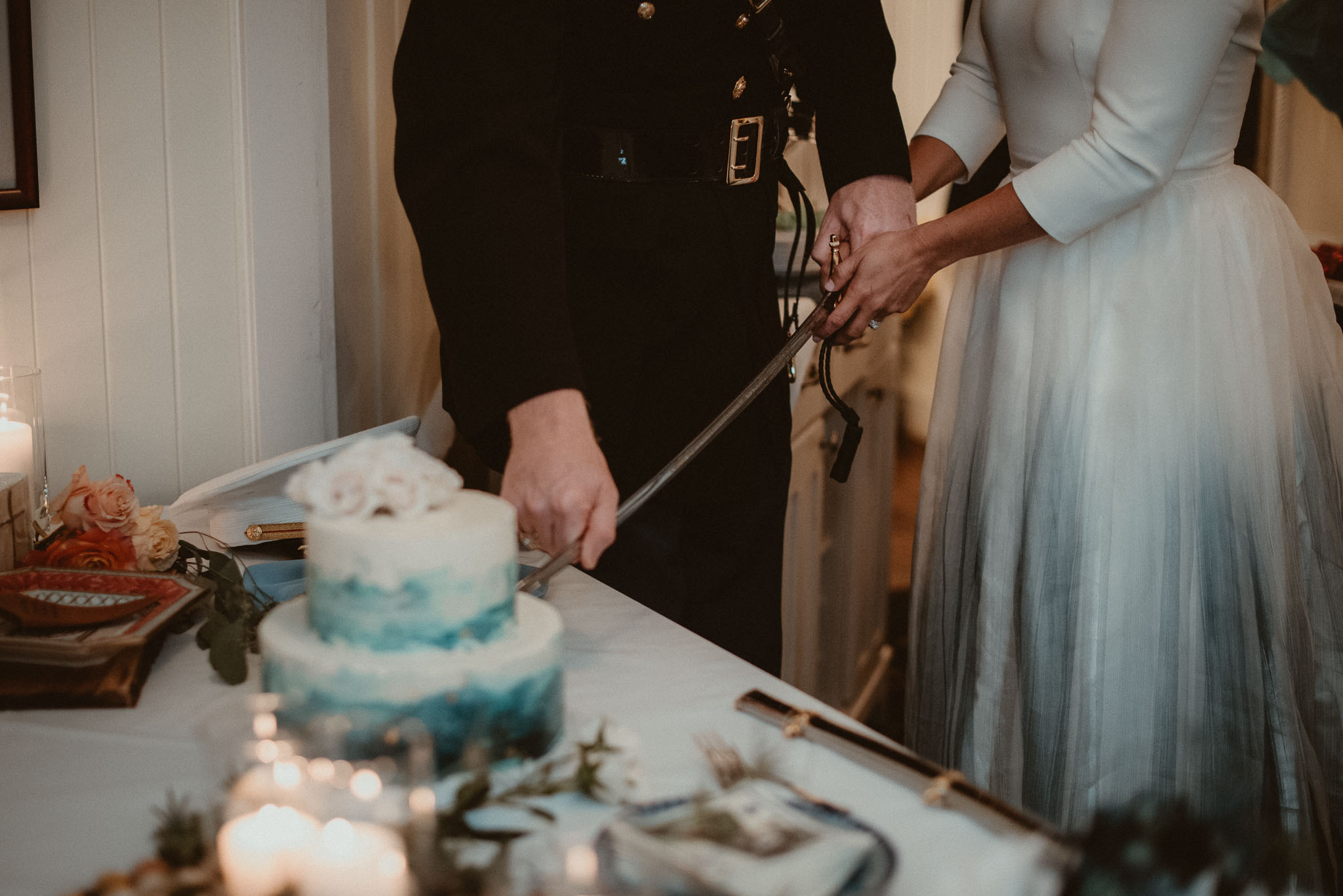 The couple cutting the wedding cake with the grooms sword.
