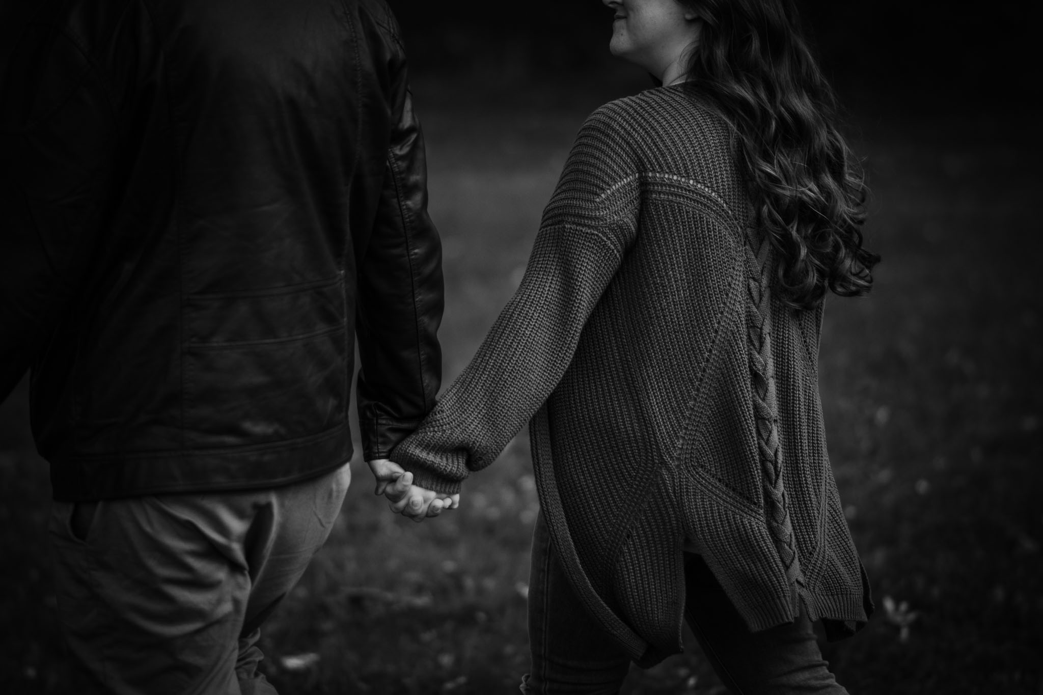Hand holding moment while walking through park in black and white