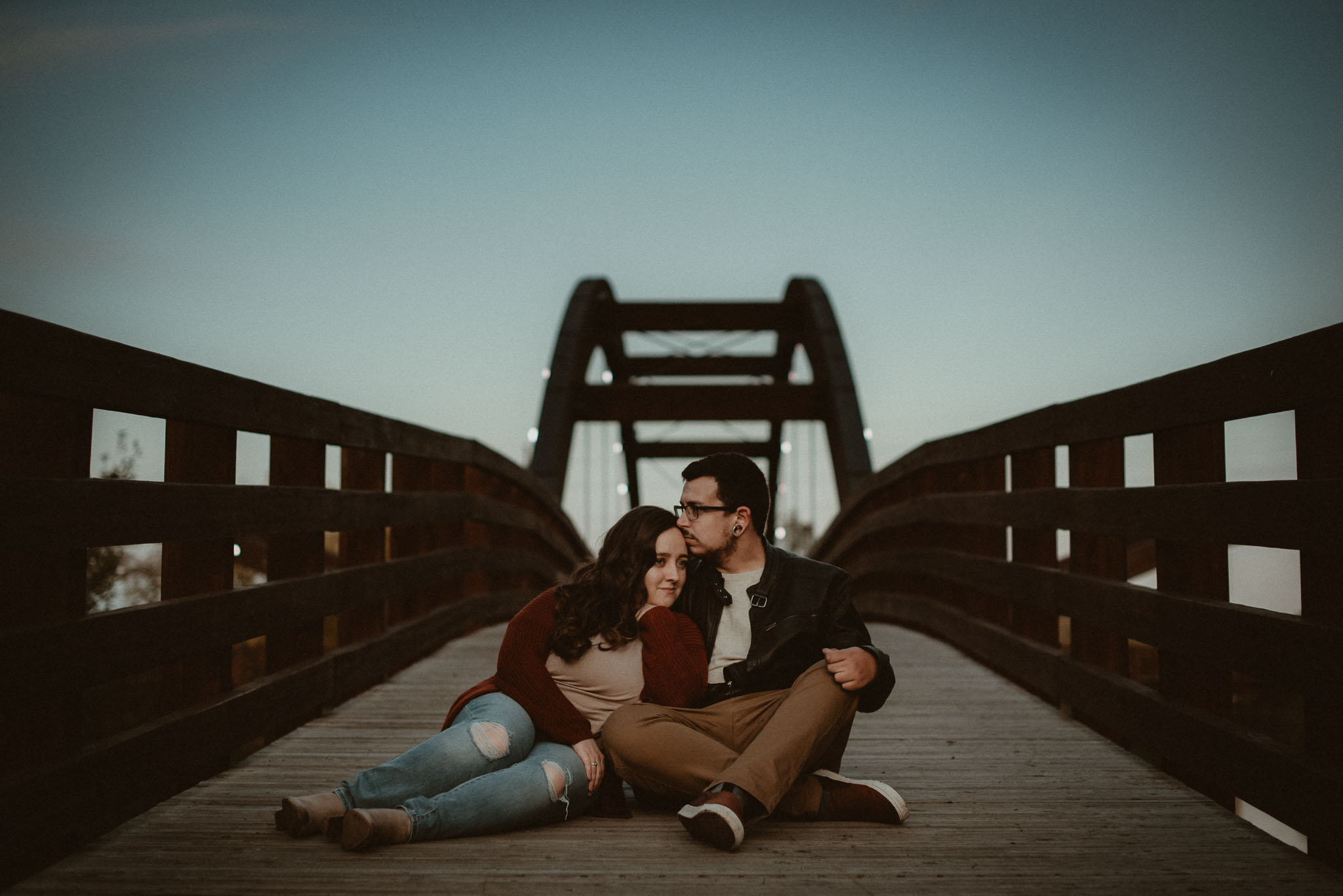 Couple sitting embracing one another on The Tridge Bridge