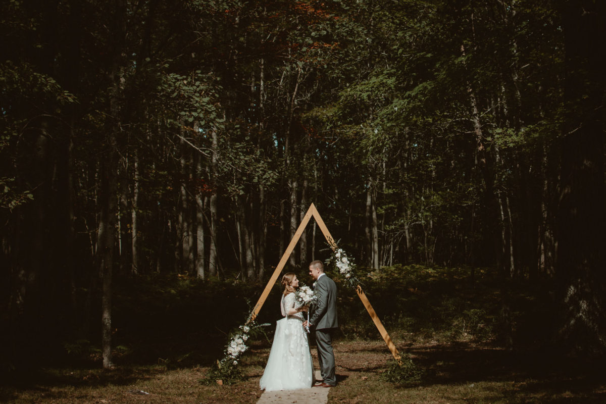 Bride & Groom gazing at each other in front of flowery triangle arch in the woods.