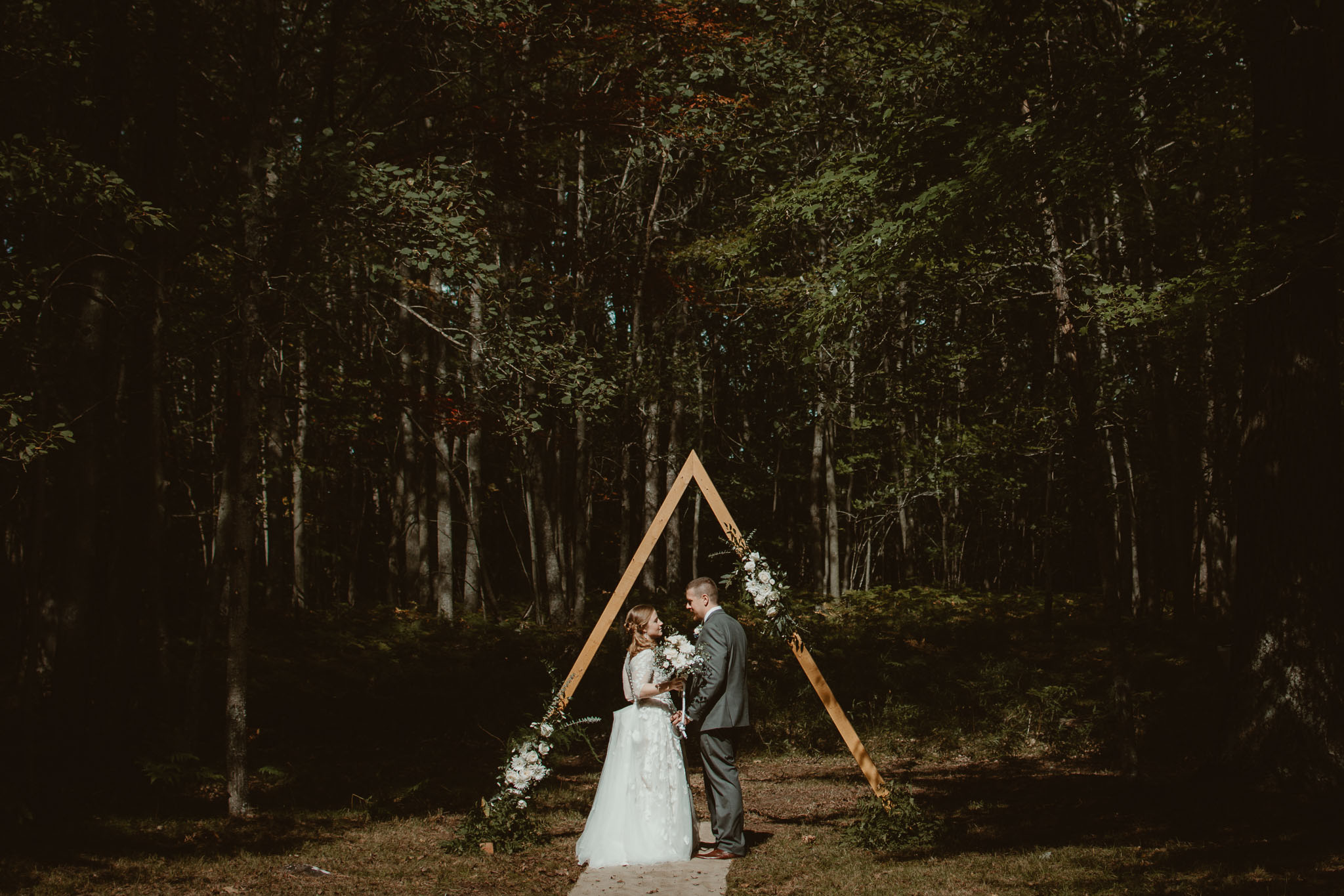 Couple standing together holding hands in front of ceremony triangle arch in the woods.