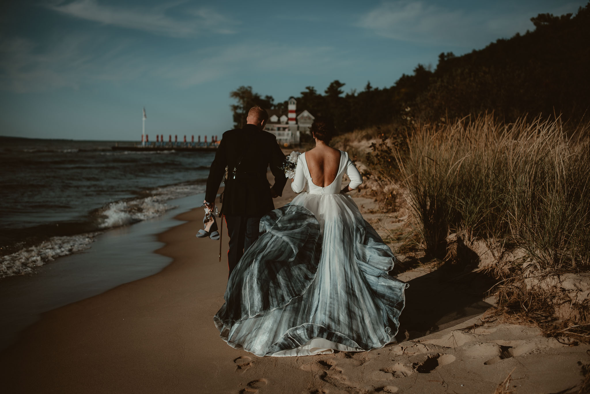 Groom in dress blues carrying brides shoes walking along sandy beach with dress flowing in wind.